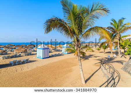 A view of sandy El Duque beach with tropical palm trees in Costa Adeje town, Tenerife, Canary Islands, Spain - stock photo