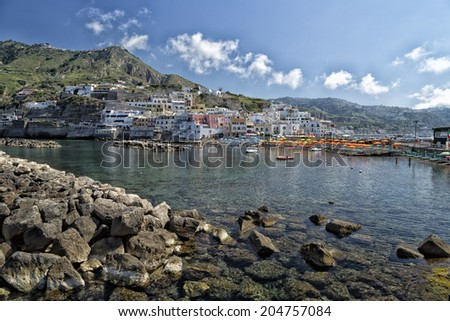 A view of Sant'Angelo in Ischia island in Italy: Tyrrhenian sea, rocks,  water, umbrella, sand and old typical houses in the island in front of Naples in Campania region in a sunny day - stock photo