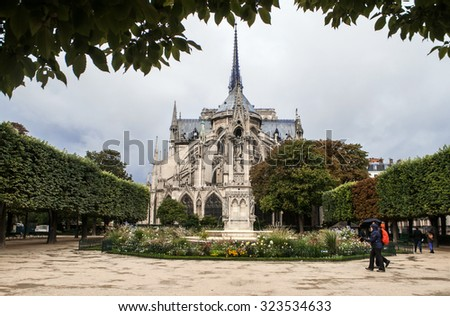 A view of the back front of the Notre Dame de Paris church in a rainy day against the overcast sky and two people walking near the church and sharing one umbrella