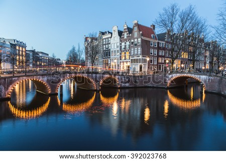 A view of the bridges at the Leidsegracht and Keizersgracht canals intersection in Amsterdam at dusk. Bikes and buildings can be seen. - stock photo