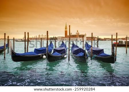 A view of the Church of San Giorgio Maggiore on the island of the San Giorgio Maggiore with gondolas parked in the water canal on Riva degli Schiavoni in Venice, Italy. - stock photo