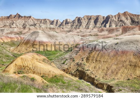 A view of the colored mounds in one of the valleys of the Badlands National Park in South Dakota that shows off the range of colors in the hills. - stock photo