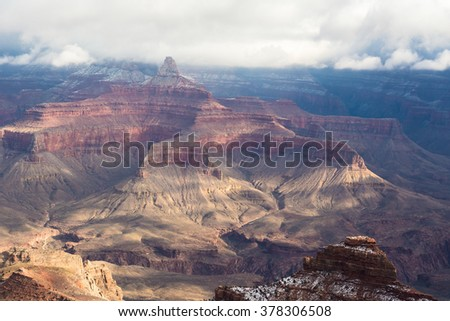 A view of the colorful hills covered with snow in the Grand Canyon in winter, when the sun is shining through the clouds