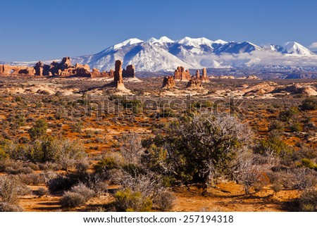 A view of the desert red rocks and the snow capped mountains around Arches National Park - stock photo