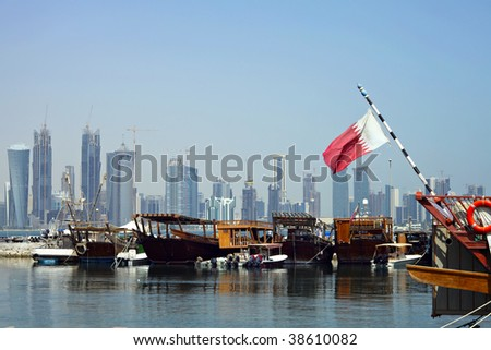 A view of the dhow harbour in Doha, Qatar, with the high-rise development across Doha Bay, a fusion of tradition and modernity which the Qataris are keen to develop The national flag is on the right. - stock photo