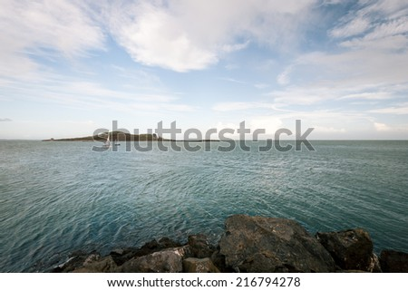 A view of the Irish Sea from the coast near Malahide, Ireland, with some recreational yachts and a small island visible. - stock photo