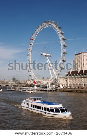 a view of the london eye with a river boat going past