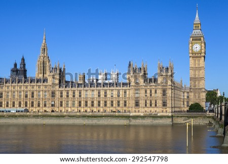 A view of the magnificent Palace of Westminster over the River Thames in London.  The towers of Westminster Abbey can be seen in the distance. - stock photo