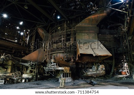 A view of the massive pig iron fueled blast furnace, now rust covered and cold, at a abandoned and now demolished steel mill.