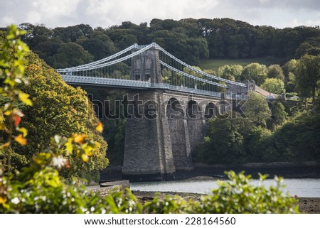 A view of the Menai suspension bridge over the Menai Straits, Anglesey, Wales, UK. - stock photo