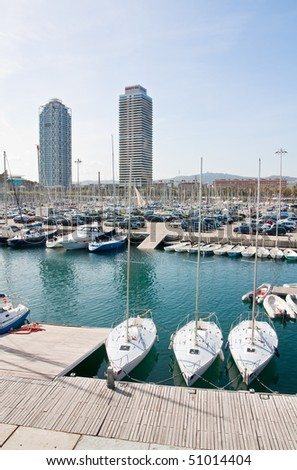 A view of the Olympic port of Barcelona city, including the Mapfre tower, the Hotel Arts tower and some ships.