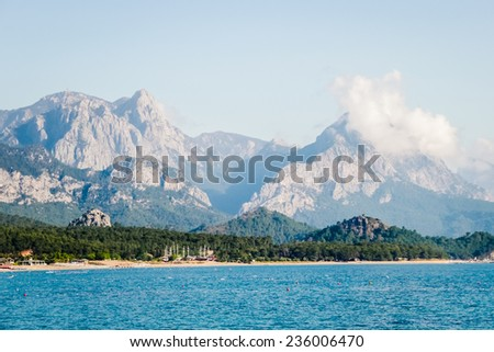A view of the peaks of the Taurus Mountains and aquamarine water in popular touristic resort on Mediterranean sea in Turkey - stock photo