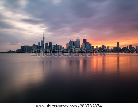 A view of the Toronto Skyline at sunset with reflections in the water. Taken with a long exposure. - stock photo