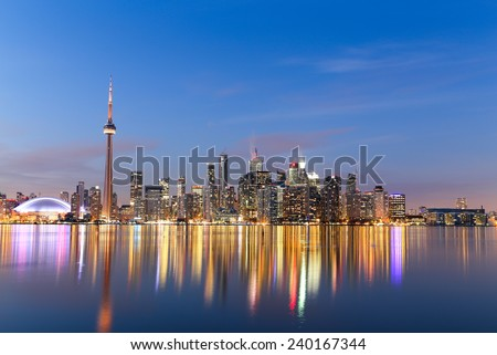 A view of the Toronto Skyline at twilight in the winter showing buildings and reflections in the water
