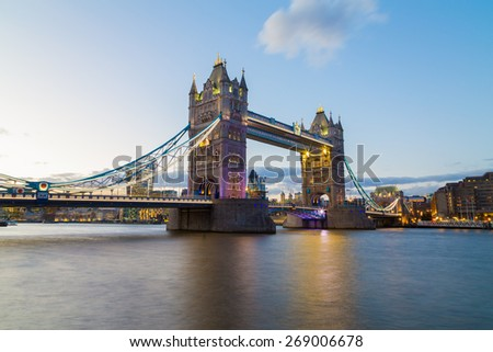 A view of Tower Bridge at Dusk. Buildings from the City of London can be seen in the background. Copyspace can be found in the water and sky. - stock photo
