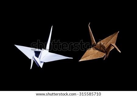 A view of two origami cranes made from brown and white recycle paper on black background - stock photo