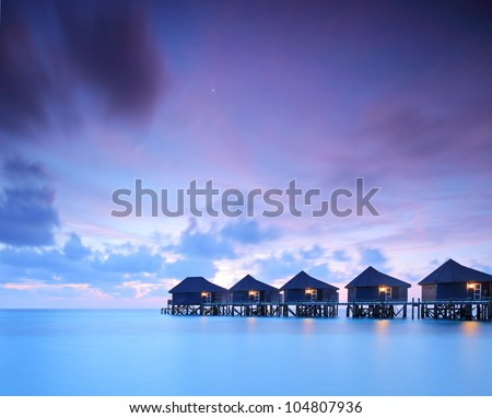 A view of water villa cottages at sunset on island of Kuredu, Maldives, Lhaviyani atoll
