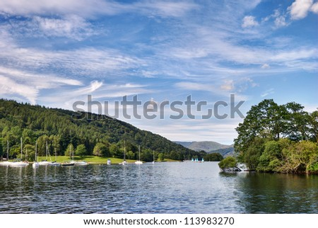 A view of Windermere in the English Lake District from Ferry house, with small pleasure boats and wooded slopes. - stock photo