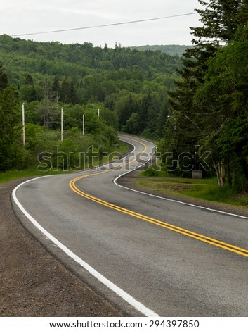 A view of windy roads in Cape Breton in the summer months. There is space for text - stock photo