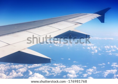 A View of Wing of an Airplane from Window Seat Overlooking Clouds and Sky - stock photo