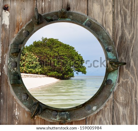 A view of Woman Key, Key West, Florida, through a old rustic porthole. - stock photo