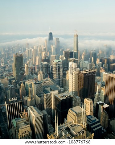 A view on a day with Clouds rolling over Chicago city downtown Skyline with aerial view of  buildings covered partially with clouds - stock photo