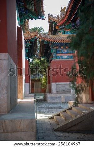 A view on a narrow street with old Chinese buildings on a territory of the Temple and museum of Confucius, Beijing, China.