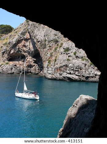 A view on an anchoring sailboat through a window in a cave... - stock photo