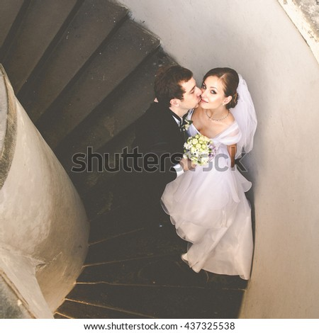 A view on the kissing wedding couple standing on the spiral stairs