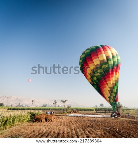 A view over the Nile floodplain near Luxor, Egypt, of a group of tour operators inflating a hot air balloon. - stock photo