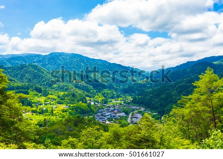 A view overlooking Tsumago village above the Magome-Tsumago portion of ancient Nakasendo Route from high angle viewpoint and former grounds of Tsumago castle in Japan on a blue sky day. Horizontal
