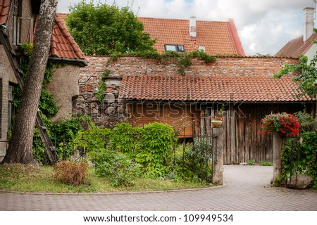 a view to small garden with old house and tiled roofs - stock photo