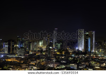 A view to the east, depicting the cityscape of downtown Tel-Aviv and its neighboring city Ramat-Gan at night. This is the central skyscraper area in the biggest metropolis in Israel. - stock photo