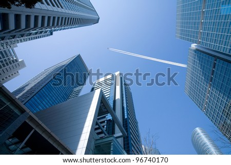 A view up through tall skyscrapers to a patch of blue sky with a jetliner flying overhead. - stock photo