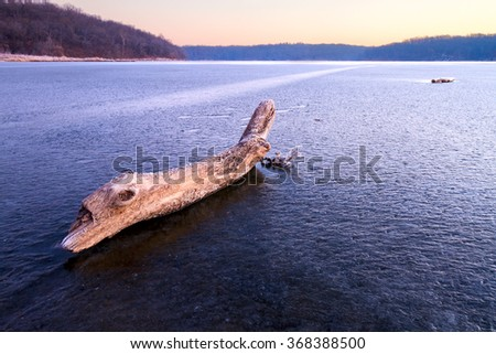 A viewpoint from on an ice covered lake of a log on the ice looking towards the shoreline at dusk - stock photo
