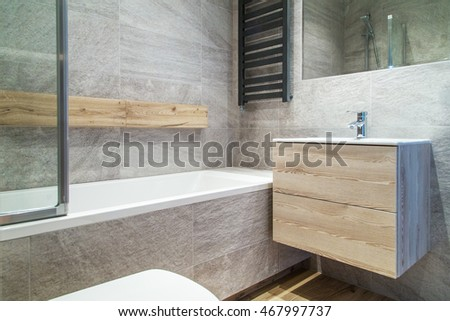 A vieww of a modern bathroom with concrete look walls
