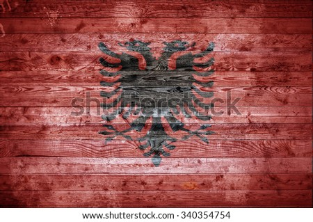 A vignetted background image of the flag of Albania painted onto wooden boards of a wall or floor. - stock photo