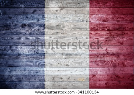 A vignetted background image of the flag of France painted onto wooden boards of a wall or floor. - stock photo