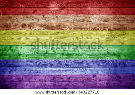 A vignetted background image of the flag of Gay Pride onto wooden boards of a wall or floor. - stock photo