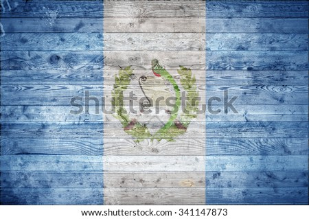 A vignetted background image of the flag of Guatemala painted onto wooden boards of a wall or floor.