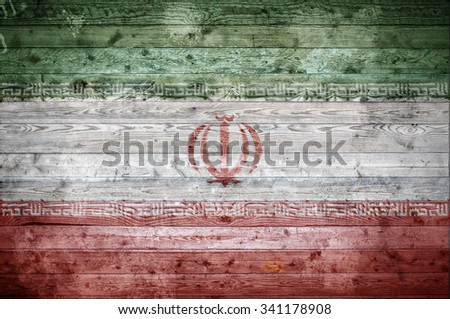 A vignetted background image of the flag of Iran painted onto wooden boards of a wall or floor. - stock photo