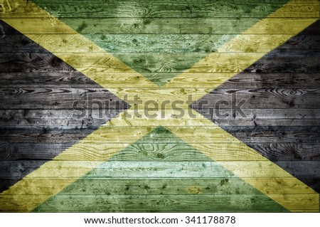 A vignetted background image of the flag of Jamaica painted onto wooden boards of a wall or floor. - stock photo