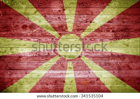 A vignetted background image of the flag of Macedonia painted onto wooden boards of a wall or floor. - stock photo