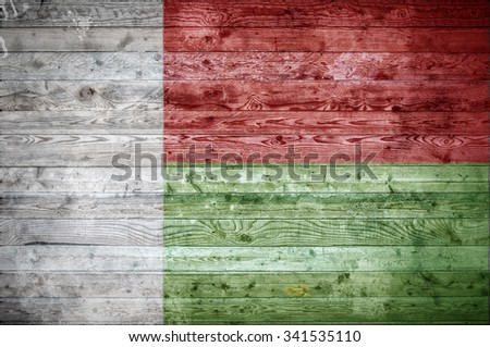 A vignetted background image of the flag of Madagascar painted onto wooden boards of a wall or floor. - stock photo