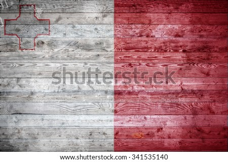 A vignetted background image of the flag of Malta painted onto wooden boards of a wall or floor. - stock photo