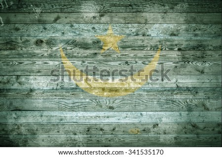 A vignetted background image of the flag of Mauritania painted onto wooden boards of a wall or floor. - stock photo