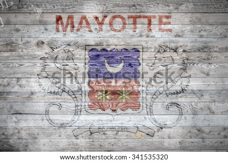 A vignetted background image of the flag of Mayotte painted onto wooden boards of a wall or floor. - stock photo