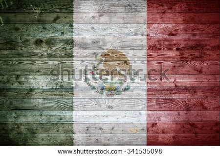 A vignetted background image of the flag of Mexico painted onto wooden boards of a wall or floor. - stock photo