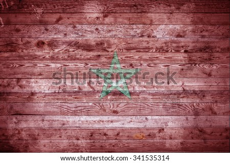 A vignetted background image of the flag of Morocco painted onto wooden boards of a wall or floor. - stock photo