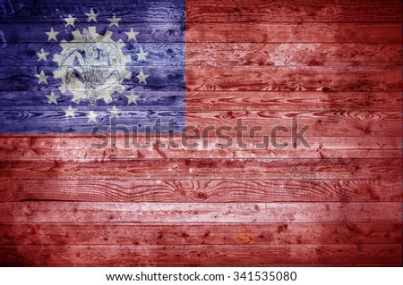 A vignetted background image of the flag of Myanmar painted onto wooden boards of a wall or floor. - stock photo